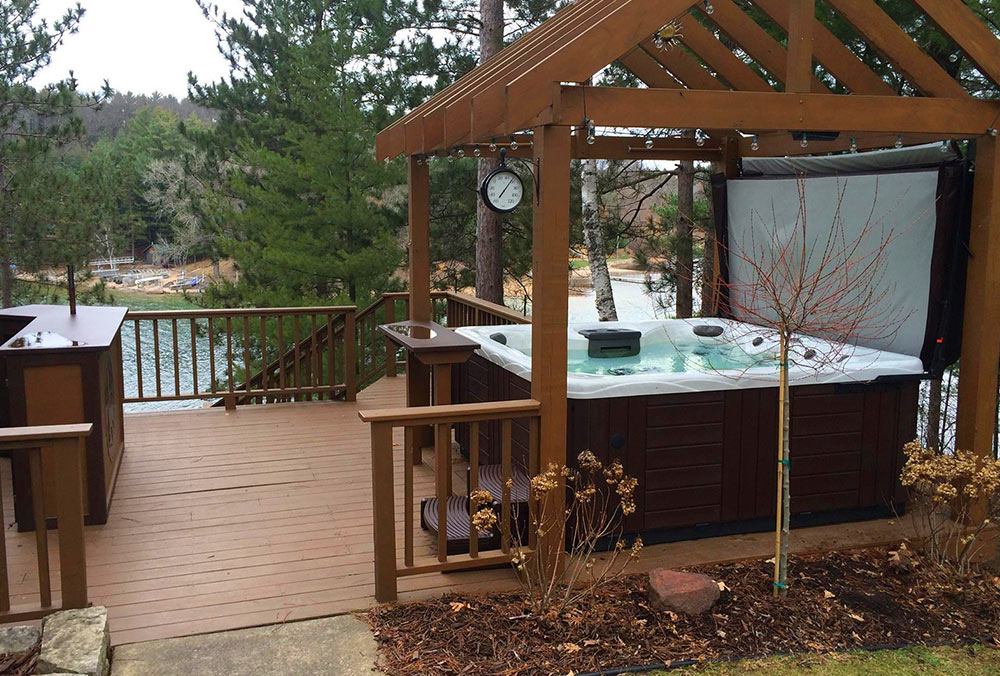 Hot tub on deck with pergola and lake view