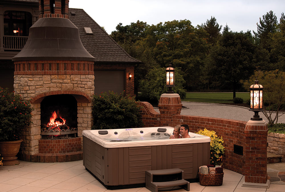 Outdoor hot tub on patio with fireplace