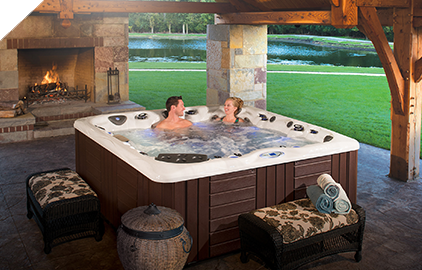 Enjoy some time spent on the patio next to a warm fireplace in your even warmer hot tub by Master Spas